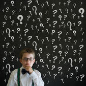 Thinking boy dressed up as business man with chalk questions marks — Stock Photo