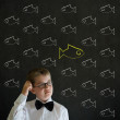 Scratching head thinking boy dressed as business man with independent thinking chalk fish — Stock Photo #25078131