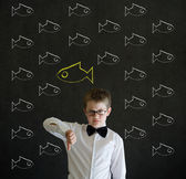 Thumbs down boy dressed as business man with independent thinking chalk fish — Stock Photo
