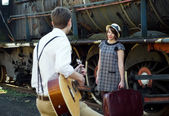 Retro young love couple vintage serenade train setting — Photo