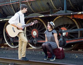 Retro young love couple vintage serenade train setting — Zdjęcie stockowe