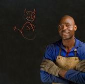 African black man industial worker chalk angel or devil on blackboard — Stock Photo