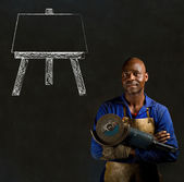 African black man industrial worker with chalk easel on blackboard background — Stock Photo