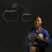 African black man industrial worker with chalk jumping fish bowls blackboard — Stock Photo
