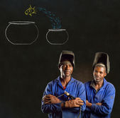 African black men industrial workers with chalk jumping fish bowls blackboard — Stock Photo