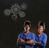 African black men industrial workers with chalk gears blackboard — Stock Photo