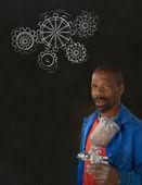 African black man industrial worker with chalk gears blackboard — Stock Photo