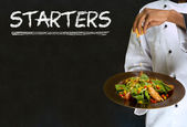 Chef with chalk starters sign on blackboard background — Stock Photo