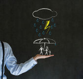 Insurance businessman holding out hand protecting family from natural disaster on blackboard background — Stock Photo
