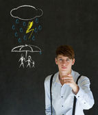 Insurance businessman protecting family from natural disaster on blackboard background — Stock Photo
