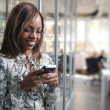 African or black American woman calling or texting on mobile cellphone telephone in office — Stock Photo #34952415