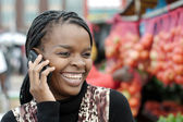 African or black American woman calling on mobile cellphone telephone in township — Stock Photo