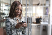 African or black American woman calling or texting on mobile cellphone telephone in office — Stock Photo