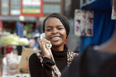 African or black American woman calling on landline telephone in Alexandra township — Stock Photo