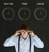 Businessman thinking with New York Paris and London chalk time zone clocks on blackboard background — Stock Photo