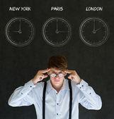 Businessman thinking with New York Paris and London chalk time zone clocks on blackboard background — Stock Photo