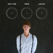 Businessman with New York Paris and London chalk time zone clocks on blackboard background — Stock Photo