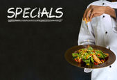 African American woman chef with chalk specials sign on blackboard background — Stock Photo