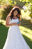 Bride texting on phone — Stock Photo