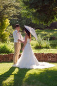 Bride and groom in garden wedding with parasol — Stock Photo