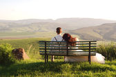 African bride and groom on bench with landscape — Stock Photo