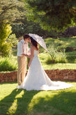 Bride and groom kissing in garden wedding — Stock Photo