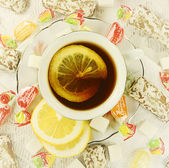 Tea with cakes, candies and lemon. — Stock Photo