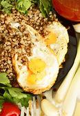 Buckwheat porridge with fried eggs. — Stock Photo