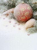 Christmas toy in the snow under the tree — Stock Photo