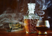 Eau-de-vie in the smoke cigars — Stock Photo
