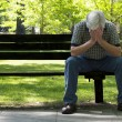 Stock Photo: Depressed Older MOn Bench With Focus On Foreground