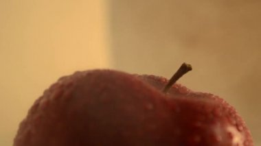 Downward crane shot of a red apple in a smoky environment.