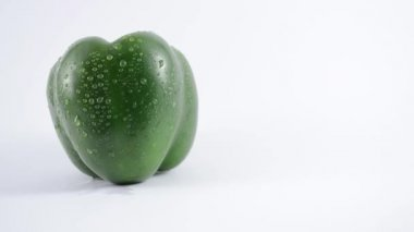 Upward crane shot of a green pepper against a seamless white background.