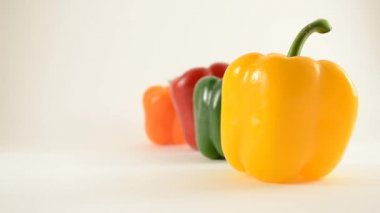 Yellow, Green, Red and Orange Peppers Against White - Line Arrangement - Crane Up — Stock Video