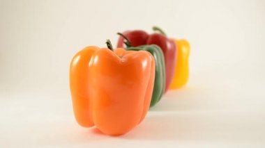 Orange, Green, Red and Yellow Peppers Against White - Line Arrangement - Dollly Left — Stock Video