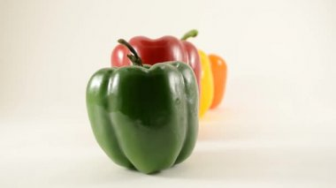 Green, Red, Yellow and Orange Peppers Against White - Line Arrangement - Dolly Left — Stock Video