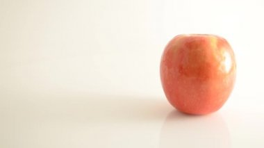 Rotating Pink Lady Apple On Acrylic Against White - Crane Down — Stock Video
