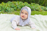Happy child lies on the green grass — Stock Photo
