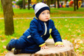 Sad child sitting on a stump — Stock Photo