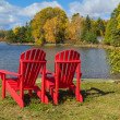 Red Adirondack Chairs on a Lake Shore — Stock Photo #17440735
