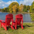 Stock Photo: Red Adirondack Chairs on a Lake Shore