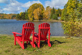 Red Adirondack Chairs on a Lake Shore — Stock Photo