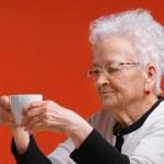 Old woman in glasses enjoying coffee or tea — Stock Photo #18951271