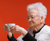 Old woman in glasses enjoying coffee or tea — Stock Photo