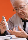 Old woman checking sugar level — Stock Photo