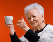 Old woman in glasses enjoying coffee or tea cup — Stock Photo