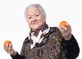 Elderly woman holding two tangerines i — Stock Photo