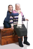 Old woman sitting on a box with her granddaughter — Stock Photo