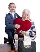 Babička s vnučkou drží polštář srdce — Stock fotografie