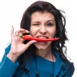 Young girl tasting chili pepper - Stock Photo